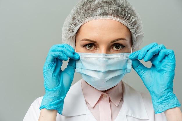Porträt einer unglücklichen jungen ärztin in einer medizinischen maske auf grauem hintergrund die ärzte müde