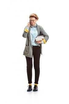 Porträt einer unglücklichen studentin, die bücher lokalisiert auf weißer wand hält