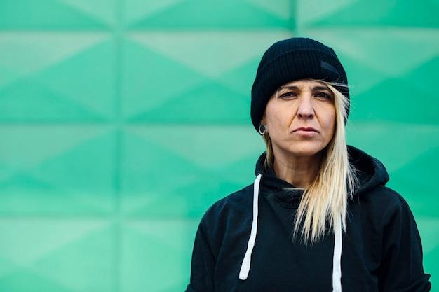 Porträt einer unhöflichen frau mit einem ernsten ausdruck, der die kamera betrachtet, eine wollmütze tragend, in einem grünen hintergrund der straße. bild mit copyspace