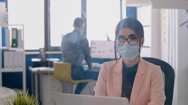 Porträt einer unternehmerin, die gesichtsmaske trägt, um eine infektion mit coronavirus während der globalen pandemie zu vermeiden. mitarbeiter, die im hintergrund im büro bei geschäftsprojekten arbeiten, die soziale distanzierung respektieren