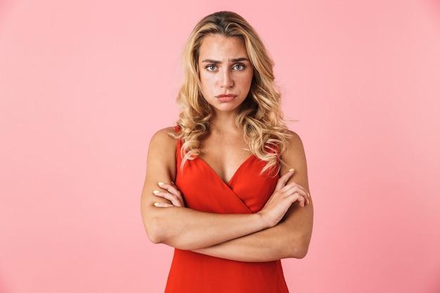Porträt einer unzufriedenen, beleidigten, süßen jungen blonden frau, die isoliert über einer rosa wand posiert