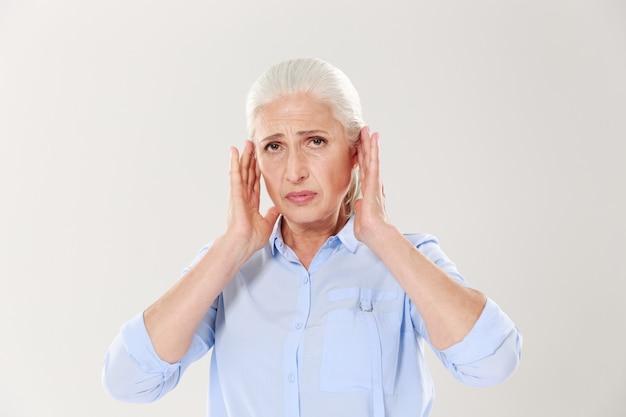 Porträt einer verärgerten alten dame, die ihren kopf berührt