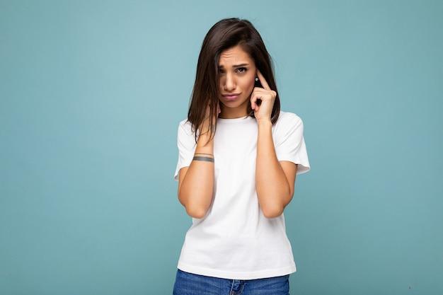 Porträt einer verärgerten, beleidigten jungen attraktiven brunet-frau mit aufrichtigen emotionen, die ein weißes t-shirt für das modell trägt, isoliert auf blauem hintergrund mit leerem raum und bedeckenden ohren.