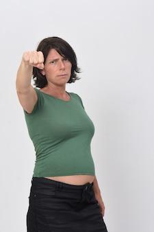 Porträt einer verärgerten frau der schwangeren frau mit erhöhtem faustweißhintergrund