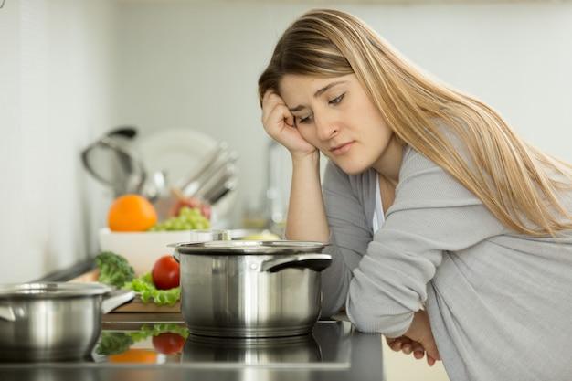 Porträt einer verärgerten frau, die suppe in der küche kocht