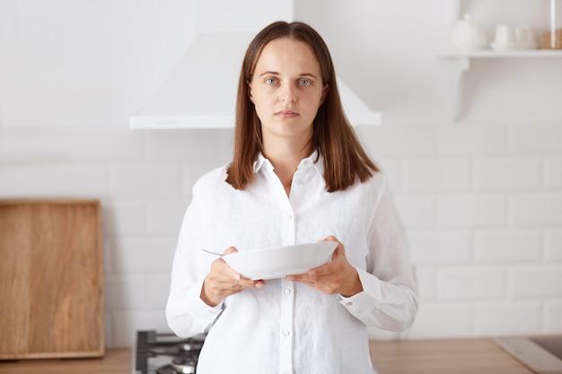 Porträt einer verärgerten jungen erwachsenen frau, die frühstückt, in der küche mit teller in den händen hält, mit sorge in die kamera schaut und legere kleidung trägt.