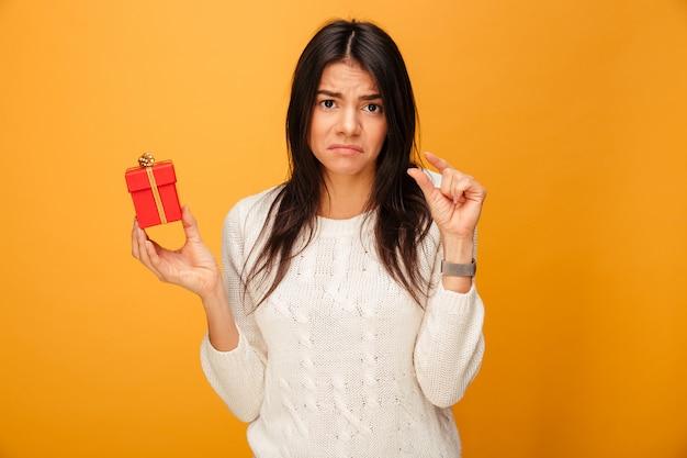 Porträt einer verärgerten jungen frau, die kleine geschenkbox hält