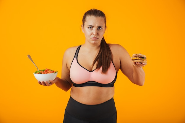 Porträt einer verärgerten übergewichtigen fitnessfrau, die sportkleidung trägt, die lokal über gelber wand steht und schüssel mit salat und burger hält