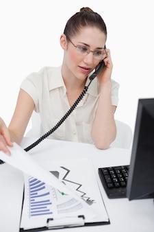 Porträt einer verkäuferin, die einen anruf beim betrachten von statistiken macht