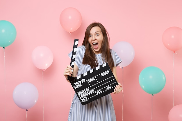 Porträt einer verrückten aufgeregten jungen frau mit offenem mund in blauem kleid, die klassische schwarze filmklappe auf pastellrosa hintergrund mit buntem luftballon hält. geburtstagsfeier konzept.