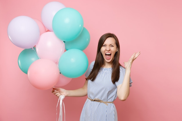 Porträt einer verrückten jungen glücklichen frau im blauen kleid, die schreiend hält, bunte luftballons, die hände einzeln auf hellrosa hintergrund ausbreiten. geburtstagsfeier, konzept der aufrichtigen emotionen der menschen.