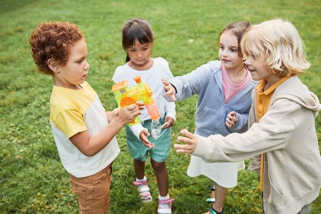 Porträt einer verschiedenen gruppe von kindern, die zusammen mit blasenspielzeug im park spielen