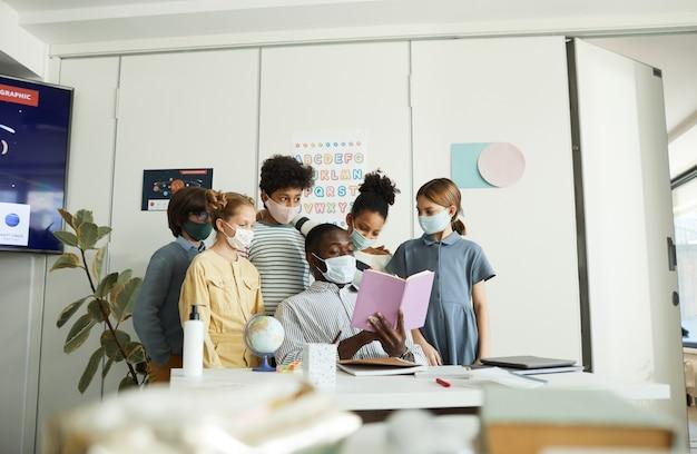 Porträt einer verschiedenen gruppe von kindern mit männlichen lehrern, die masken im schulklassenzimmer tragen, kovid-sicherheitsmaßnahmen, kopierraum