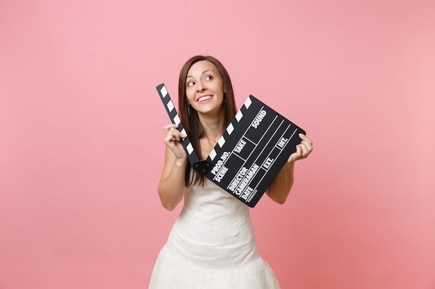 Porträt einer verträumten frau im weißen kleid, die nach oben schaut, halten die klassische schwarze filmklappe, die eine filmklappe macht