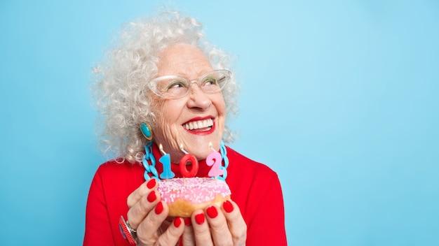 Porträt einer verträumten, fröhlichen, lockigen älteren frau, die breit gefächert beiseite lächelt, denkt über den wunsch nach, bevor sie kerzen bläst, trägt roten pulloverschmuck, helles make-up hält leckeren glasierten donut