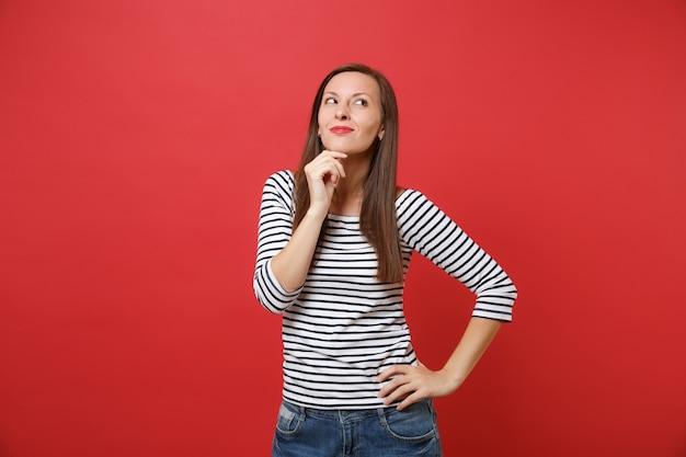 Porträt einer verträumten lächelnden jungen frau in gestreifter kleidung, die nach oben schaut, handstütze auf das kinn legen