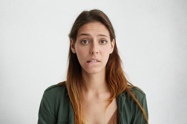 Porträt einer verwirrten frau mit langem gesicht und glatt gefärbtem haar in grüner jacke, die mit großen geöffneten augen auf ihre unterlippe beißt und zweifel und unsicherheit hat