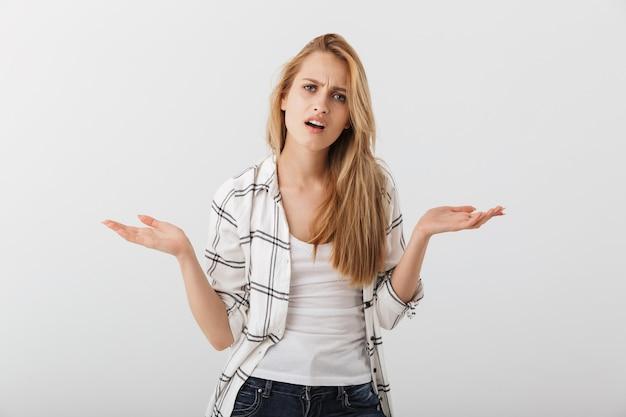 Porträt einer verwirrten jungen lässigen frau, die mit den schultern zuckt