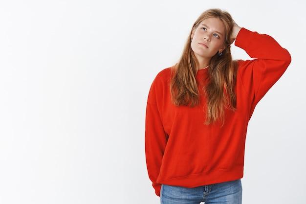 Porträt einer verwirrten, unsicheren, charmanten jungen studentin in warmem pullover, die ahnungslos am kopf kratzt und nachdenklich in die obere linke ecke schaut und nachdenklich die entscheidung mit unsicherem blick trifft
