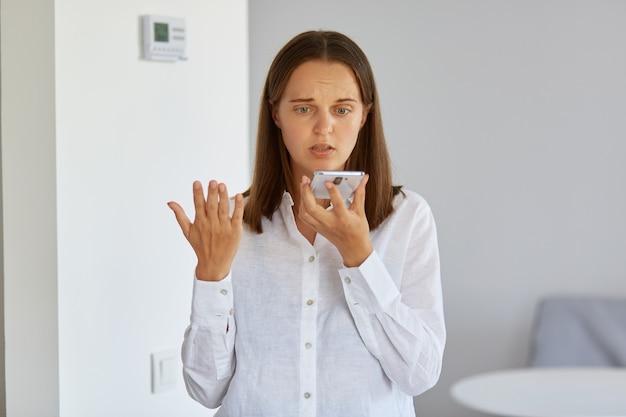 Porträt einer verwirrten verwirrten frau mit weißem hemd, die zu hause mit smartphone in den händen posiert, den arm hebt, versteht nicht, warum das gerät nicht funktioniert.