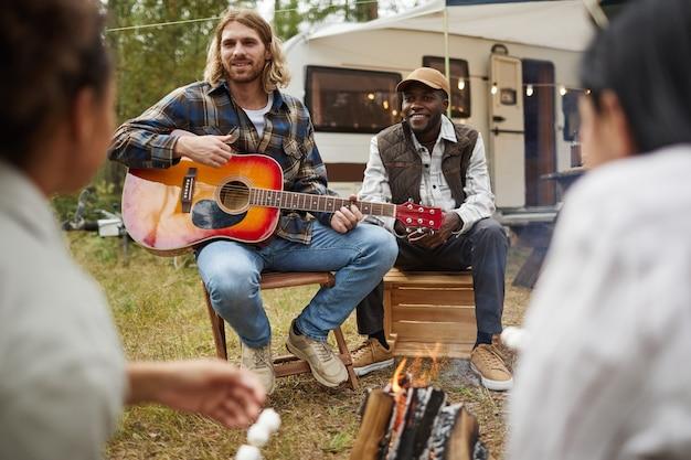 Porträt einer vielfältigen gruppe junger leute, die gitarre spielen, während sie mit freunden in waldkopien campen...