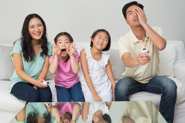 Porträt einer vierköpfigen familie, die im wohnzimmer fernsieht