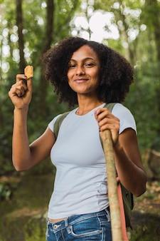 Porträt einer wanderfrau, die eine müsliriegel im dschungel isst