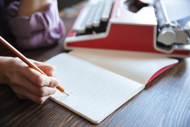 Porträt einer weiblichen hand, die bleistift über offenem notizbuch hält
