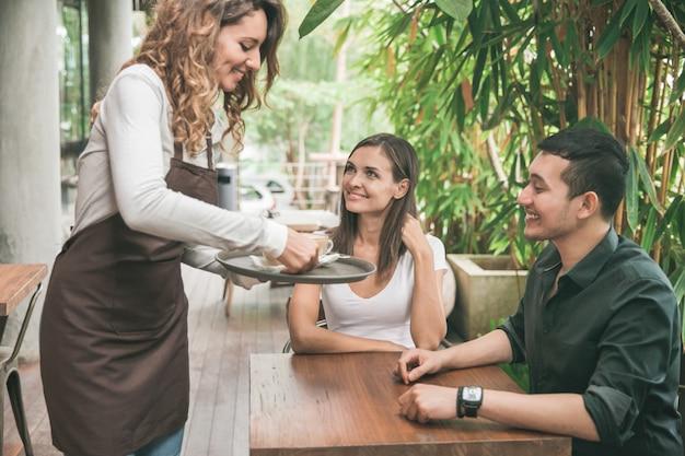 Porträt einer weiblichen kellnerin, die einem paar kunden kaffee serviert