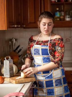 Porträt einer weinenden hausfrau beim zwiebelschneiden in der küche