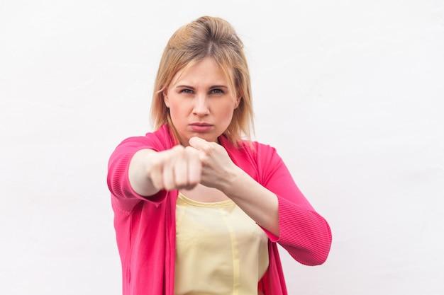 Porträt einer wütenden, ernsten blonden jungen frau in gelbem hemd und roter bluse, die mit boxfäusten steht und in die kamera schaut und schlägt. indoor-studioaufnahme, isoliert auf weißem wandhintergrund.