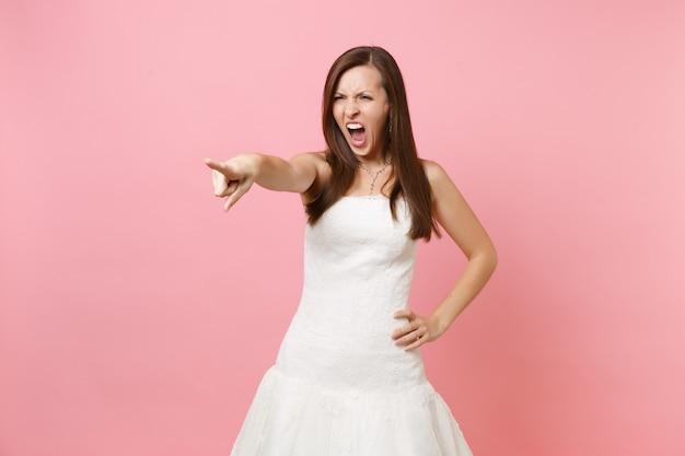Porträt einer wütenden, gereizten frau im weißen kleid, die schreiend fluchend mit dem zeigefinger zur seite zeigt