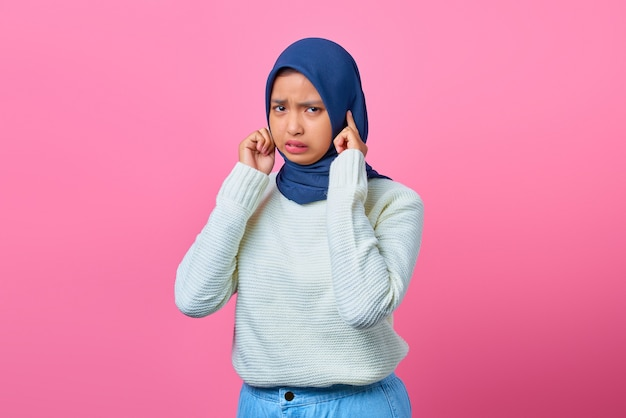 Porträt einer wütenden jungen asiatin, die ihre ohren mit dem finger bedeckt