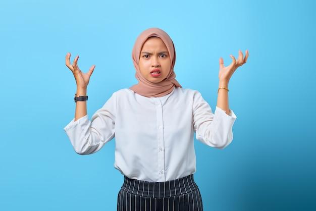 Porträt einer wütenden jungen asiatin, die mit argumenten mit erhobenen händen auf blauem hintergrund verärgert ist
