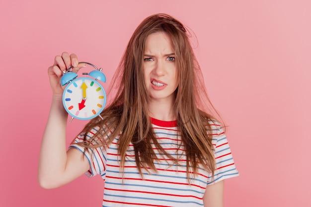 Porträt einer wütenden, müden, süßen dame mit aggressivem gesicht, die eine uhr auf rosa hintergrund hält