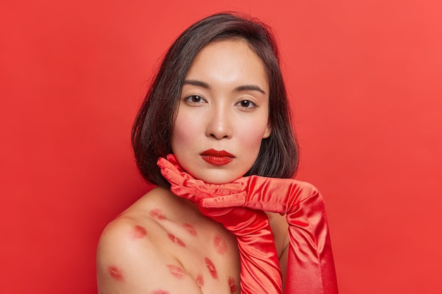 Porträt einer wunderschönen asiatischen dame mit dunklem haar hält die hände unter dem kinn steht seitlich gegen die rote wand schaut direkt in die kamera hat kussspuren auf nackten körperposen drinnen trägt lange handschuhe