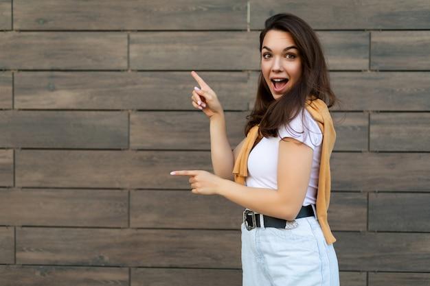 Porträt einer wunderschönen, faszinierenden, emotionalen promoterin, die auf den kopierraum für die werbung mit hipster-outfit mit aufrichtigen emotionen zeigt