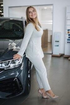 Porträt einer wunderschönen frau im schönen verkäufer des ausstellungsraums, der nach dem auto blondes haar weiblich steht