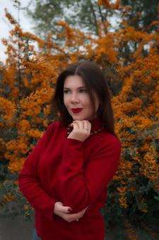 Porträt einer wunderschönen frau mittleren alters in einem herbstpark. hallo november. cooler roter pullover