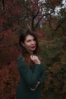 Porträt einer wunderschönen frau mittleren alters in einem herbstpark. hallo november. stilvolle erwachsene frau in einem schönen kleid