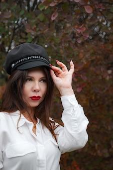 Porträt einer wunderschönen frau mittleren alters in einem herbstpark. hallo november. stylische erwachsene frau mit mütze und schwarzem mantel