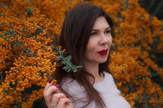 Porträt einer wunderschönen frau mittleren alters in einem herbstpark. hallo november.