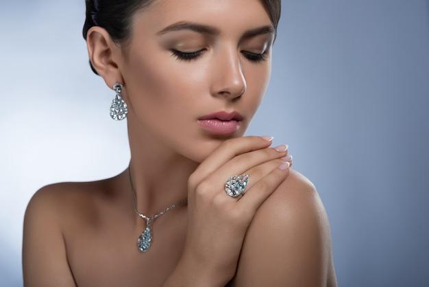 Porträt einer wunderschönen jungen eleganten frau mit diamantohrringen, ring und halskette, die mit geschlossenen augen posiert