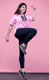 Porträt einer wunderschönen lateinamerikanischen frau des positiven körpers in einem rosa sport-hoodie, der mit hanteln auf rosa trainiert