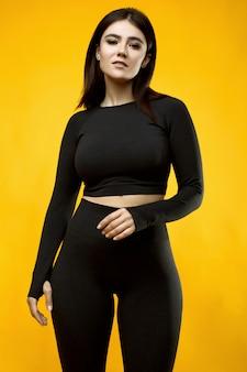 Porträt einer wunderschönen lateinamerikanischen frau des positiven körpers in einem schwarzen sportanzug, der auf gelb aufwirft