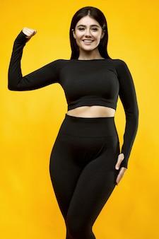 Porträt einer wunderschönen lateinamerikanischen frau des positiven körpers in einem schwarzen sportanzug, der auf gelb ausübt