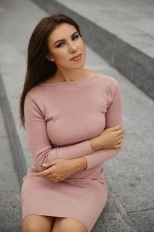 Porträt einer wunderschönen sexy vollbusigen frau mit einem perfekten körper, einer dünnen taille und breiten hüften in einem beigen, engen kleid, das im freien posiert.