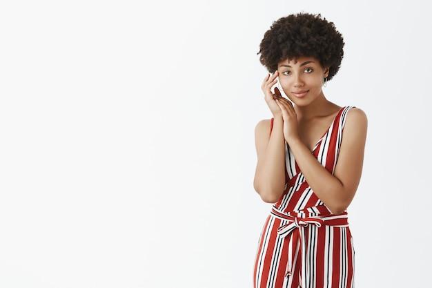 Porträt einer zarten und sinnlichen weiblichen afroamerikanerin in gestreiften overalls, die das gesicht sanft berührt und mit weichem und fürsorglichem ausdruck lächelt und sich hübsch und schön fühlt