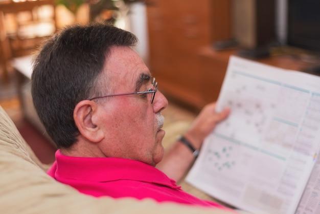 Porträt einer zeitung des älteren mannes lese