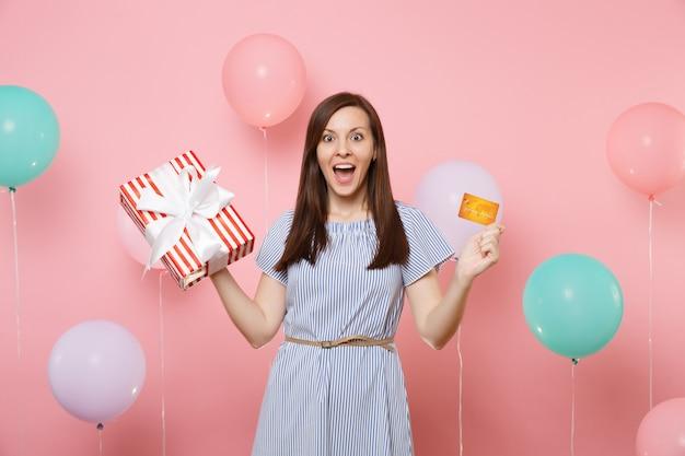 Porträt einer ziemlich aufgeregten jungen frau im blauen kleid mit kreditkarte und roter schachtel mit geschenkgeschenk auf rosafarbenem hintergrund mit bunten luftballons. geburtstagsfeier, menschen aufrichtige emotionen.